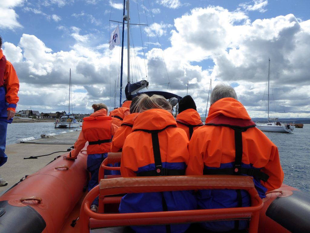 Shows rigid inflatable boat going out looking for whales and whisky in Scotland.